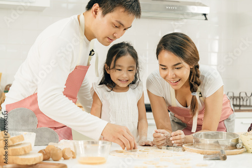 Fotomural  Young asian family cooking food in kitchen