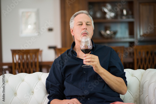Photo sur Toile Alcool Portrait of a mature man enjoying a glass of red wine at home