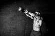 Leinwanddruck Bild - Young strong sweaty focused fit muscular man with big muscles holding heavy kettle bell for swing cross training hard core workout in the gym black and white