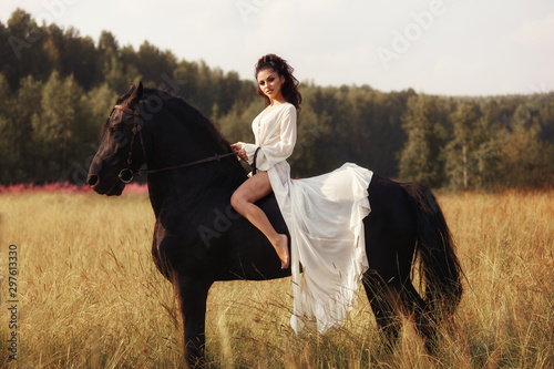 Girl in a long dress riding a horse, a beautiful woman riding a horse in a field in autumn. Country life and fashion, noble steed