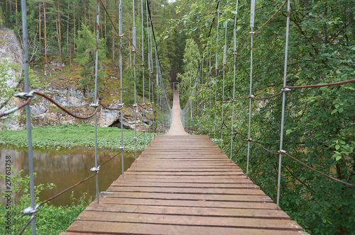 karst suspension bridge over the river Serga in the forest in cloudy cloudy weather in national Park in Sverdlovsk region cervine stream