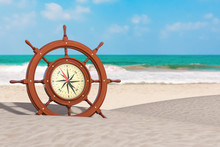 Vintage Wooden Ship Steering Wheel With Rare Compass On An Ocean Deserted Coast. 3d Rendering