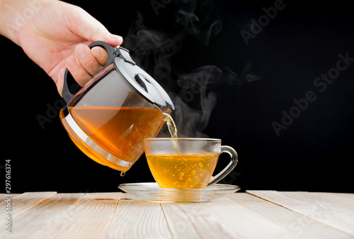 Freshly brewed tea is pouring into a tea cup placed on a wooden table. With warm light sunshine, black background