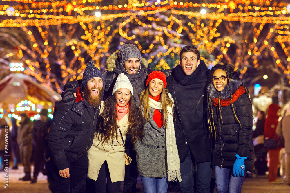 Fototapety, obrazy: Laughing people standing on Christmas market