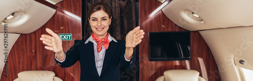 panoramic shot of smiling flight attendant in uniform with outstretched hands in Wallpaper Mural