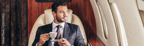 Fototapeta panoramic shot of handsome businessman in suit holding cup of coffee in private plane obraz