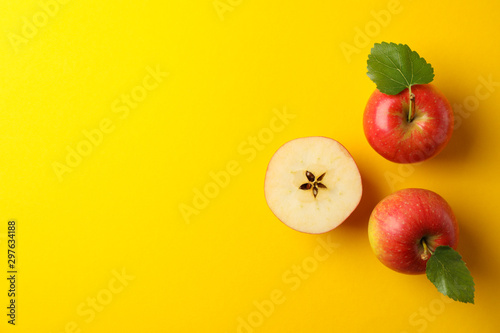 Fotografía  Flat lay with red apples on yellow background, space for text