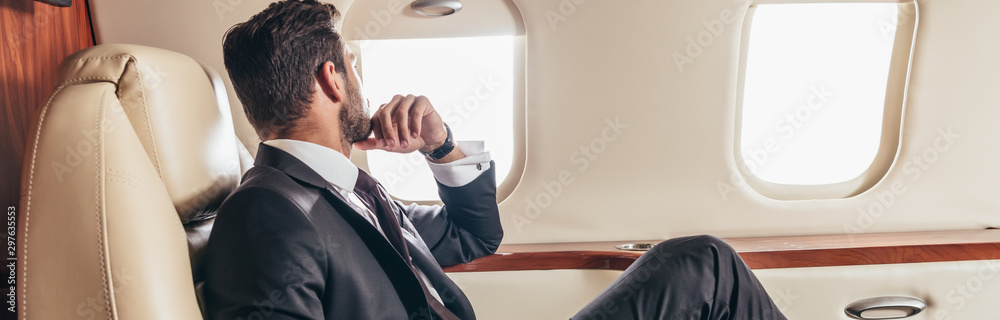 Fototapeta panoramic shot of businessman in suit looking through window in private plane