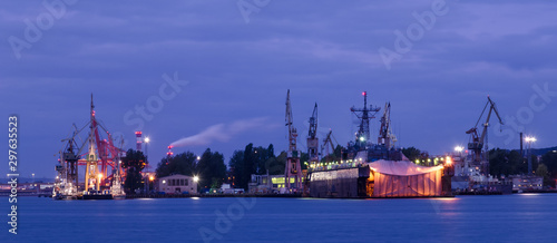 Fototapeta EVENING HARBOR LIFE - Illuminated waterfront and repair dock of the Navy shipyar