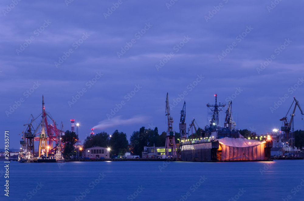 EVENING HARBOR LIFE - Illuminated waterfront and repair dock of the Navy shipyard i Gdynia
