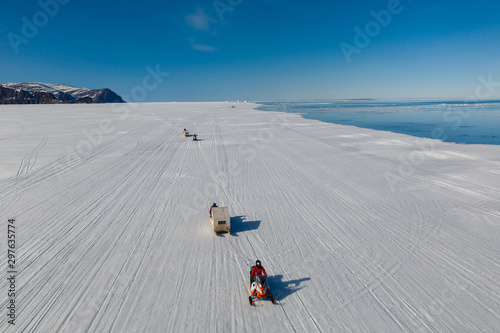 Fotografie, Obraz  Aerial drone photo of tourists travelling by Qamutiik on the sea ice near Sirmil
