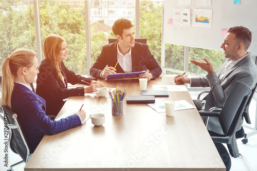 Group of business people discussing business in a meeting room with one empty chair Wallpaper Mural