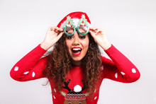 Studio Portrait Of Young Woman With Dark Skin And Long Curly Hair Wearing Tight Santa Claus Hat And Christmas Outfit. Ugly Sweater Concept. Close Up, Copy Space For Text, Isolated Background.