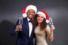 Studio Portrait Of Young Couple, Boyfriend Wearing Suit & Girlfriend In Sexy Dress With Glitter, Santa Claus Hat And Christmas Outfit. Close Up, Copy Space For Text, Isolated Background.