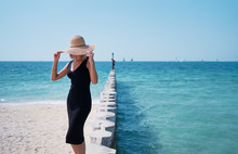 Lonely And Calm. Vacation On The Sea. Young Woman In Hat Walking  On Beach.
