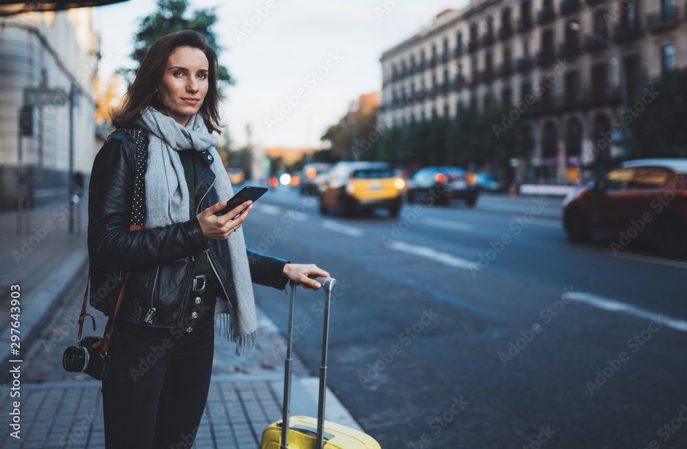 Fototapety, obrazy: Traveler woman with suitcase calling mobile phone waiting yellow auto taxi in evening street europe city Barcelona. Girl tourist using smartphone technology internet online gadget cellphone