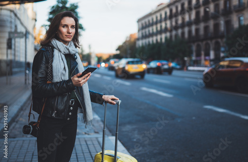 Fotomural Traveler woman with suitcase calling mobile phone waiting yellow auto taxi in evening street europe city Barcelona