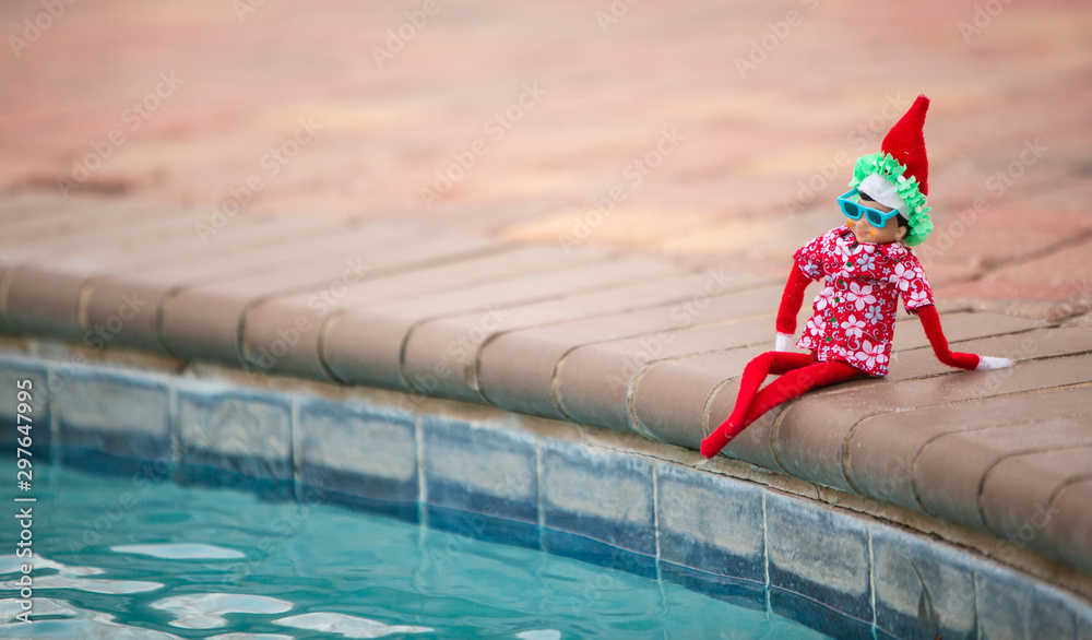 Fototapety, obrazy: Christmas Elf lounging by the swimming pool celebrating time off. Christmas retail sales marketing clearance promotion