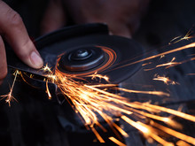 Man Sharpen Axe By Grinder In The Dark With Sparks