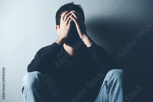 sad man sitting on ground on dark background Wallpaper Mural