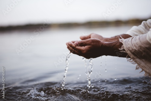 Foto Closeup shot of a person wearing a biblical robe drinking water with hands