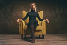 Beautiful Young Stylish Woman In Black Wear Sitting In Yellow Armchair.