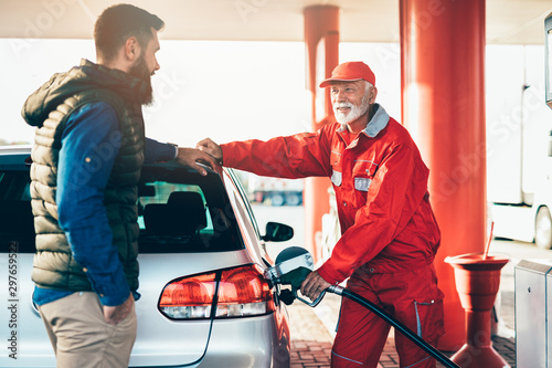 Young handsome adult man together with senior worker standing on gas station and fueling car Canvas Print