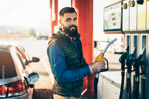 Young handsome adult man standing on gas station and fueling his car Poster Mural XXL