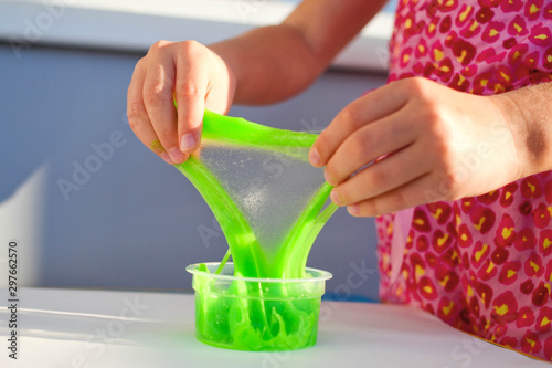Fotografía Close up of a little girl is hand playing a green slime