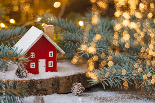 Miniature wooden house on the snow over blurred Christmas decoration background, toned