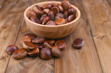 Cup of chestnuts on a wooden background. Autumn harvest and ripe fruits. Free space for text.