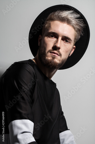 Attractive guy in black clothes with the hat on his head and stylish hairdo Canvas Print