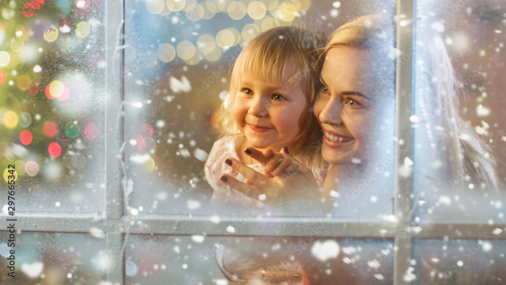 Fototapety, obrazy: On Christmas Eve Mother and Daughter Looking Through Window with Snowy Effect. Garland Shines Bright on a Window.