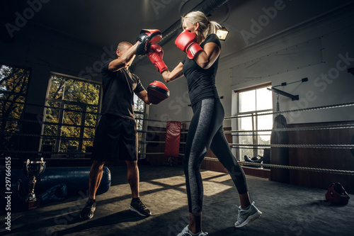 In the dark gym on the ring experienced trainer and young woman has a kick boxing fight Canvas Print