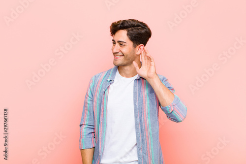 Leinwand Poster  young handsome man smiling, looking curiously to the side, trying to listen to g