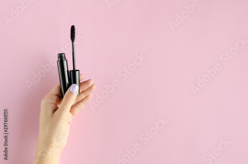 Hand with black mascara composition on pink background. Canvas Print