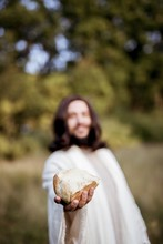 Vertical Shot Of Jesus Christ Handing Out Bread With A Blurred Background