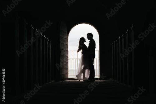 Valokuvatapetti Silhouette of loving couple hugging while standing in doorway on black backgroun