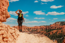 Hiker Woman In Bryce Canyon Hiking Looking And Enjoying View During Her Hike Wearing Hikers Backpack. Bryce Canyon National Park Landscape, Utah, United States. Sunny Day, Clear Skies, Hot Summer.
