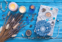 Blue Tarot Cards Deck And White Magic Book On Blue Wooden Table Background.