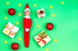 Leinwandbild Motiv Christmas background. Toy elf, present boxes, red baubles, confetti glitter stars on light green background