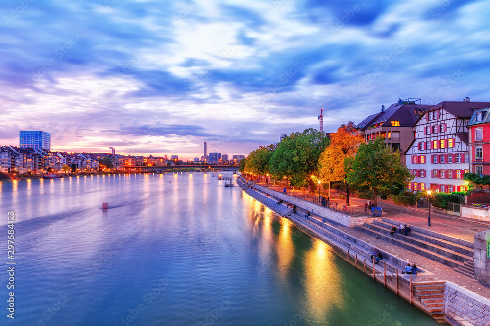 Besel, Switzerland, autumn. Beatiful twilight cityscape of Swiss city Basel, view over  Rhine river beneath incredible dramatic sky. City lights of Basel, popular travel and business destination.
