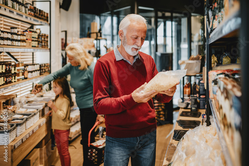 Happy grandmother and grandfather with granddaughter shopping together in grocery store or supermarket. Consumerism concept.