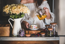 Young Caucasian Woman Pouring Freshly Brewed Green Tea From Glass Pot Into Beautiful Vintage Porcelain Cup At Kithcen Counter. Autumn Tea Time Concept