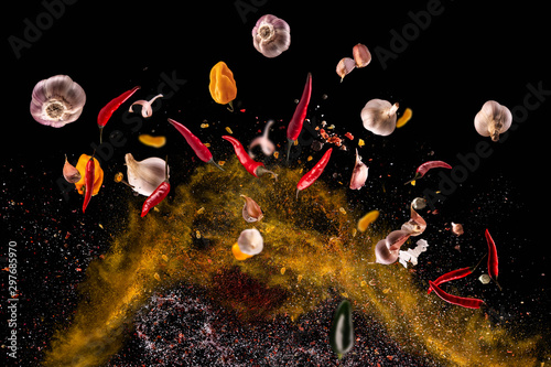 Photo Hot red pepper, garlic, different spices powder flying on a black background Mot
