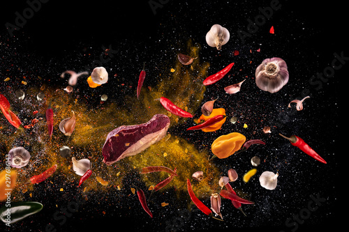 Hot red pepper, garlic, different spices powder meat stakes flying on a black ba Wallpaper Mural