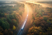 Train In Beautiful Forest In Fog At Sunrise In Autumn. Aerial View Of Moving Commuter Train In Fall. Colorful Landscape With Railroad, Foggy Trees With Orange Leaves, Mist. Top View. Railway Station