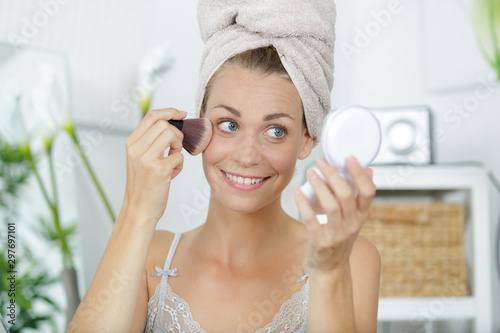woman applying blusher looking in a compact mirror Wallpaper Mural