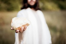 Biblical Scene - Of Jesus Christ Handing Out Bread With A Blurred Background