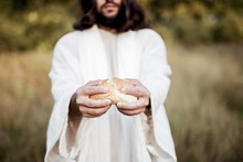 Biblical Scene - Of Jesus Christ Splitting The Bread With A Blurred Background